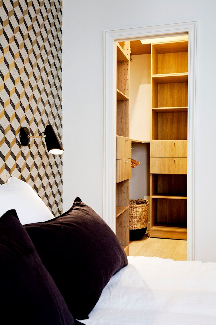 Vestidor en el dormitorio con interiores terminados en madera clara