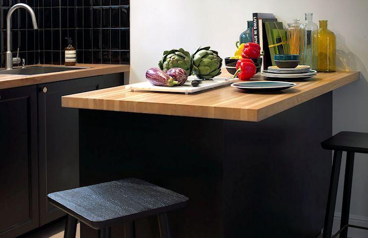 Tanto los muebles de cocina como la isla tienen mesadas de madera, cortando un poco con el negro