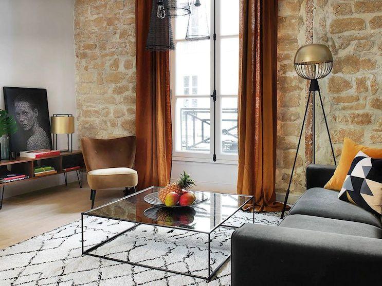 La mesa de centro repite los materiales del divisor de ambientes, haciendole juego. La alfombra blanca con motivos enmarca el sector del living y aporta un color contrastante a la decoración