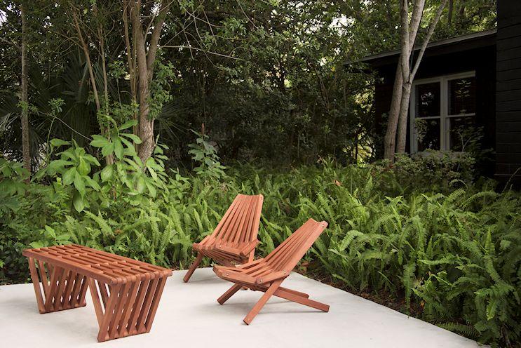 Deck de cemento alisado con helechos de fondo que añaden volumen y densidad al diseño del jardín