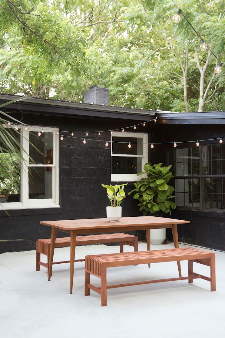Fondo luego de la renovación: paredes negras, carpintería blanca, patio pavimentado con cemento