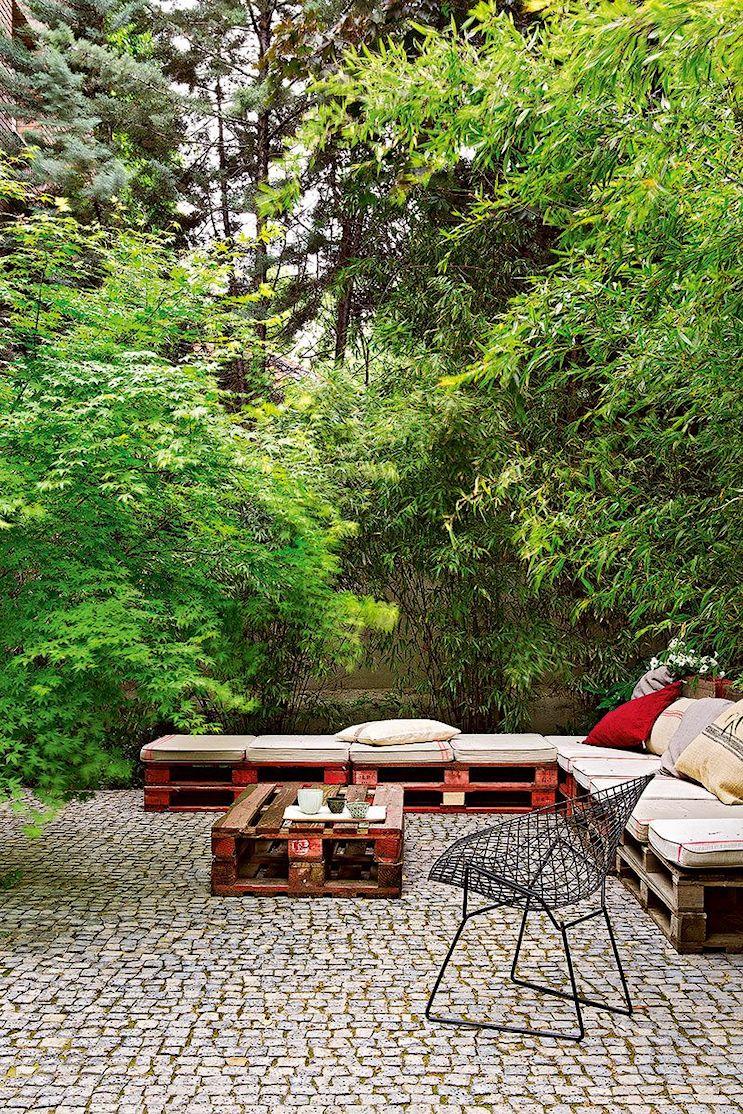 Sector del livng exterior en el jardín con pisos de adoquines