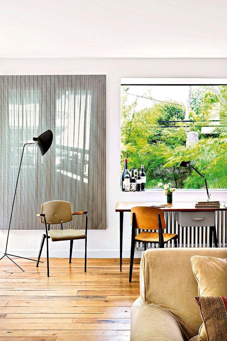 Espacio de trabajo bajo un paño fijo de vidrio que incorpora el verde el exterior al interior de la casa