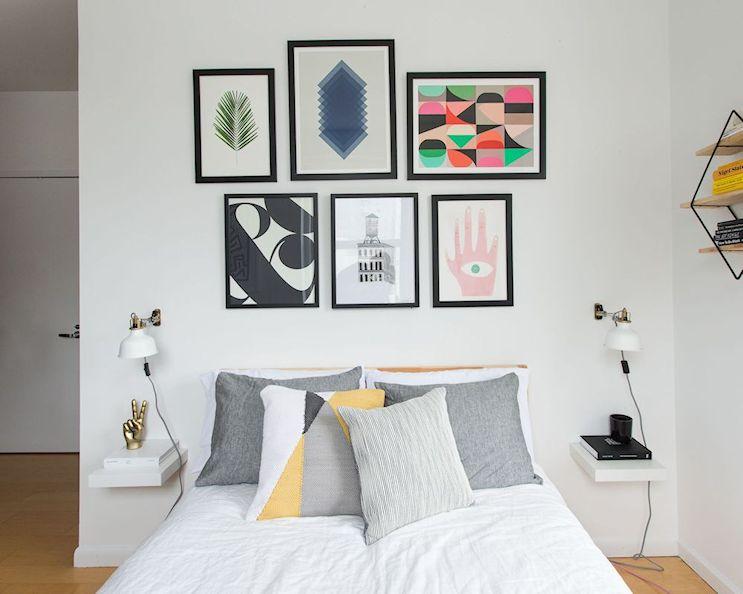 Monoambiente pequeño minimalista: sector del dormitorio en un rincón y decorado con cuadros y elementos gráficos