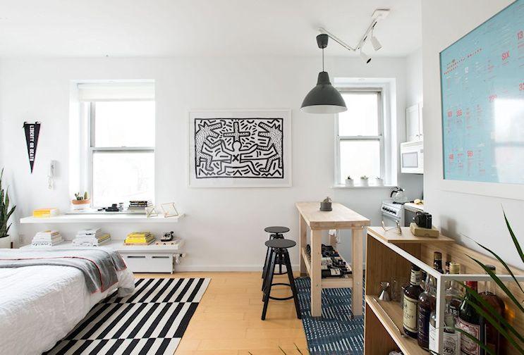 Monoambiente pequeño minimalista: el área de estar está formada por una isla de cocina que separa ambos espacios y un par de taburetes