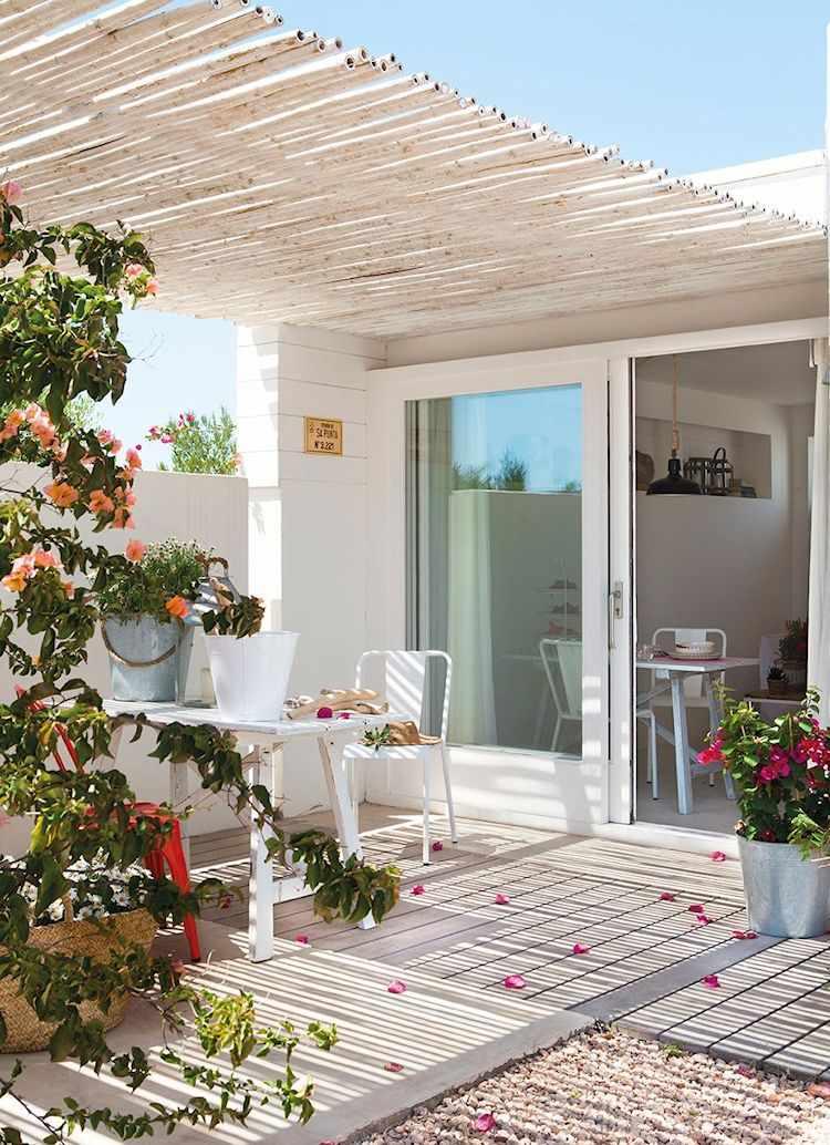 Un techo de cañas de bambú pintadas de blanco tampiza la luz del sol en el patio