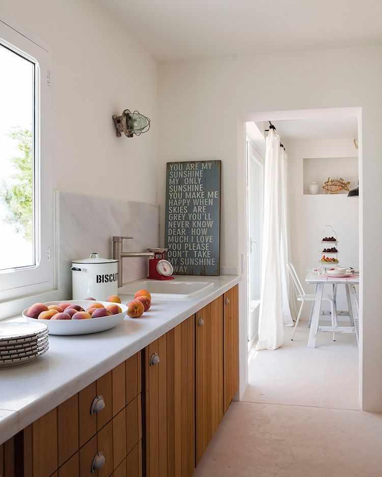 Cocina pequeña de diseño lineal con muebles de madera clara con tiradores rústicos y mesada de mármol blanco