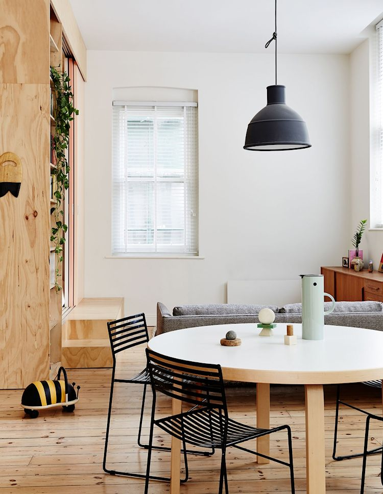Vista hacia el living del departamento donde se ve la estructura de madera terciada que contiene los dormitorios, integrándose a la decoración de forma natural y con estilo