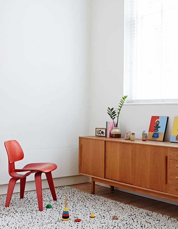 Living con muebles de diseño danés y una silla Eames pintada de rojo