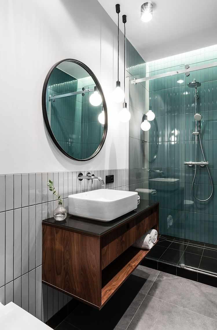 Mueble de baño o vanitory de madera oscura y suspendido en la pared. Bacha de diseño moderno rectangular con bordes redondeados y grifería de pared cromada.