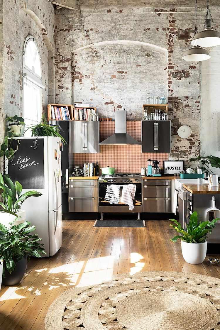 Loft de diseño en antiguo edificio industrial: cocina con muebles de acero inoxidable y mesada de madera.