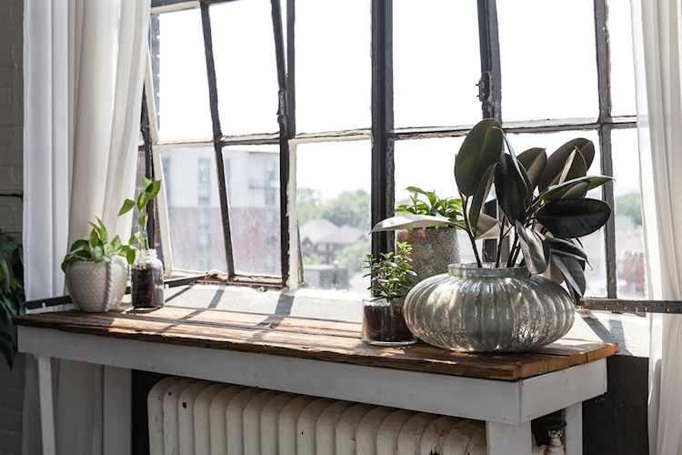 Más muebles rústicos, aquí sobre un radiador antiguo, con plantas para decorar
