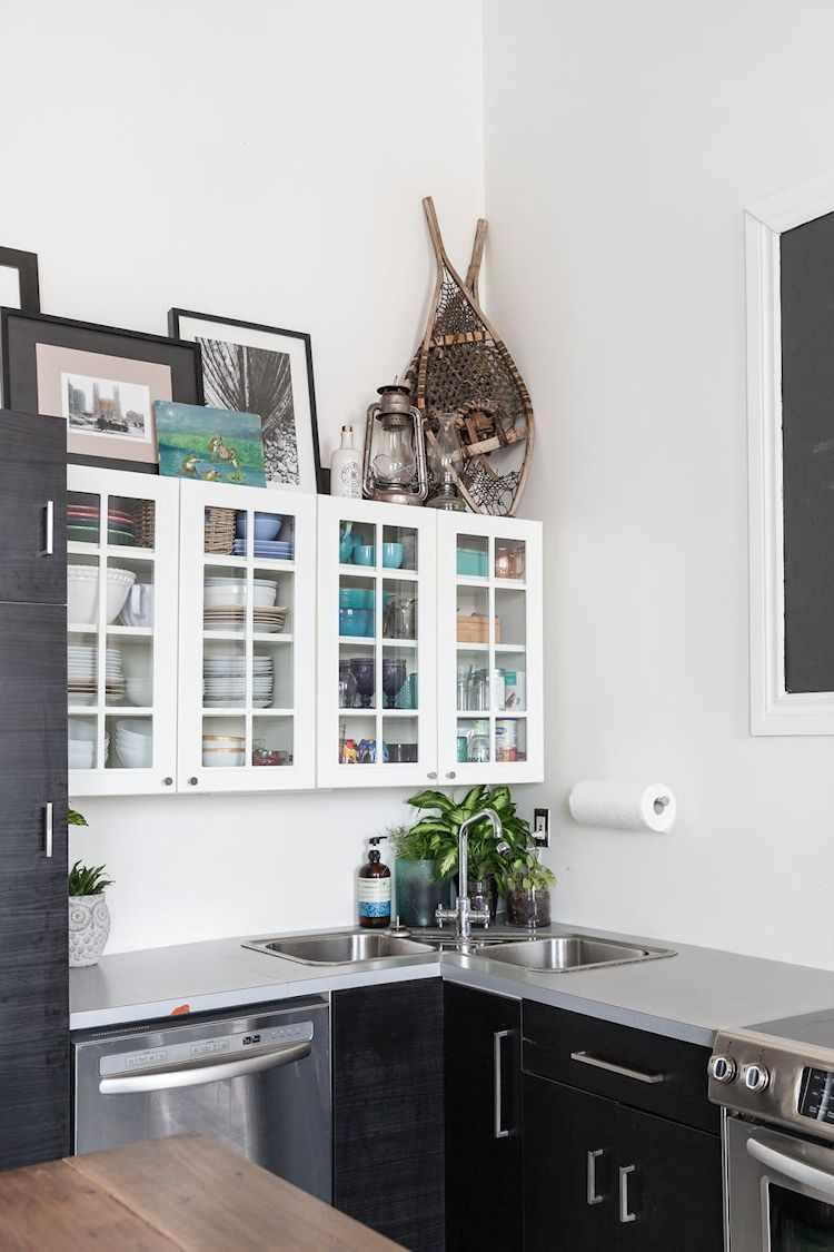 Muebles de cocina bajomesada en madera oscura y alacena con vidrio repartido en color blanco. Sobre ella, cuadros en blanco y negro y objetos náuticos