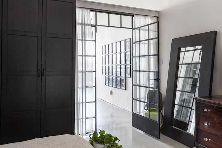 Para dividir el dormitorio del ambiente principal se instaló una estructura metálica con puerta y vidrio repartidos que repite el diseño de los grandes ventanales.