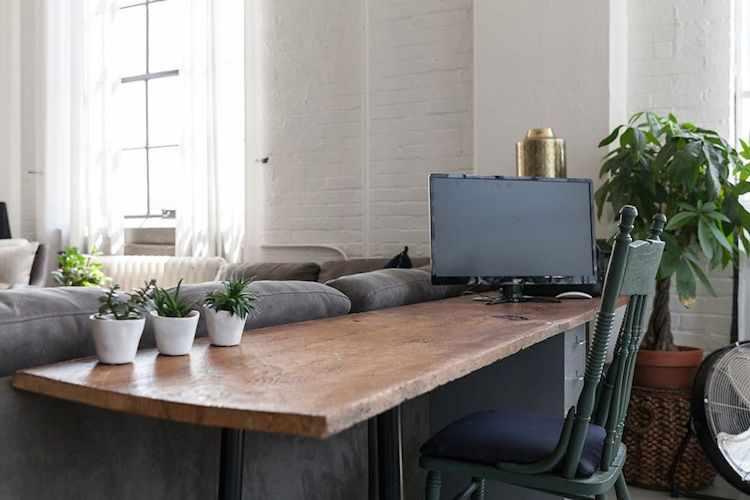 Espacio de trabajo, creado con un escritorio con tapa de madera rústica y una cajonera metálica, apoyado sobre la parte de atrás del sofá esquinero para aprovechar el espacio.
