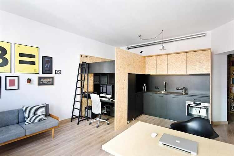 Cama ubicada sobre un mueble que contiene el escritorio y la cocina, realizado en OSB