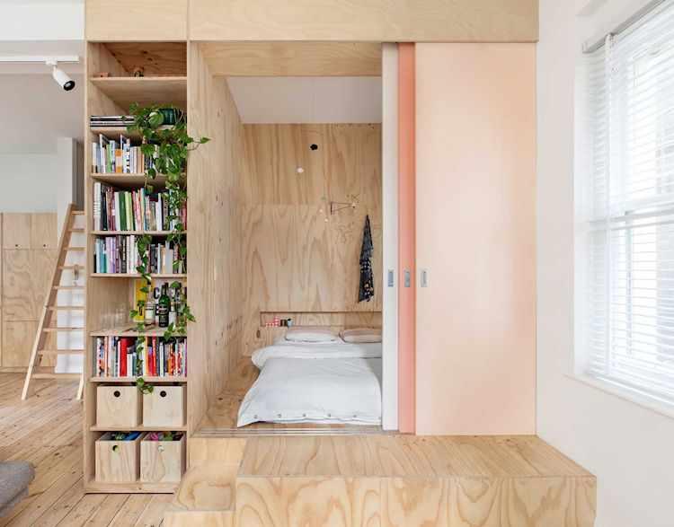 Plataforma en madera terciada para dividir el espacio del dormitorio del ambiente principal y sumar espacio de guardado debajo
