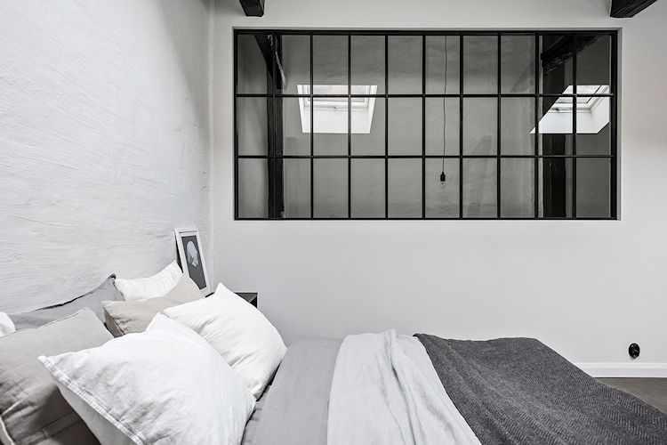 Para darle luz a la escalera, en una pared se instaló una ventana metálica con vidrio repartido.