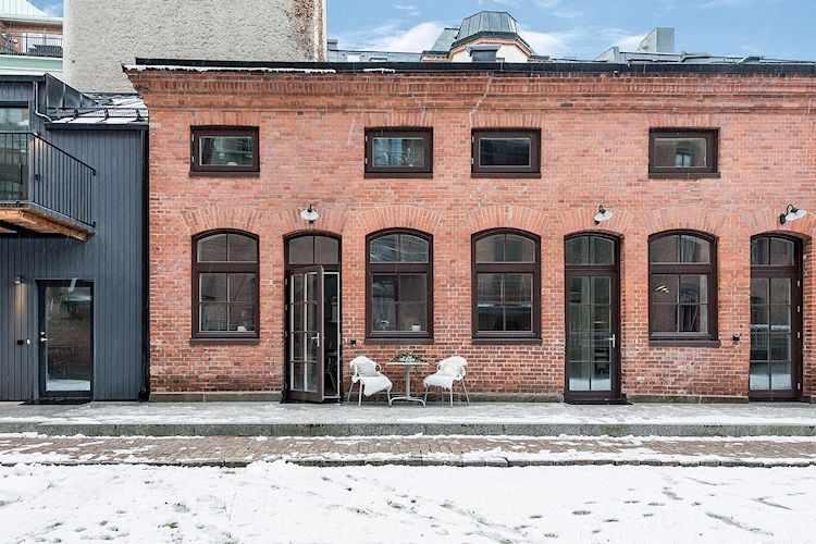 Exterior del dúplex con ladrillo visto y estética estilo industrial.
