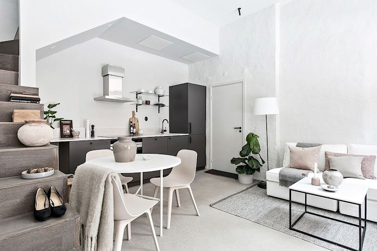 Comedor con mesa redonda y sillas contemporáneas, ubicado junto a la cocina y al costado de la escalera.