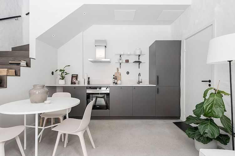 Cocina moderna de diseño lineal con muebles grises y espacio para ocultar la heladera.