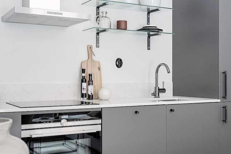 Los artefactos de cocina y grifería en acero inoxidable acentúan el estilo moderno de la cocina.