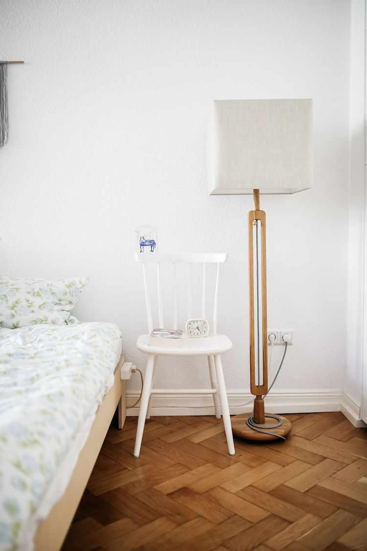 Silla como mesa de luz y lámpara de pie con base de madera y pantalla blanca