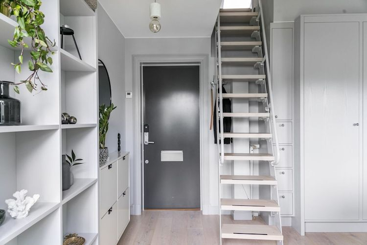 Escalera fija y empinada que ocupa muy poco espacio en el living