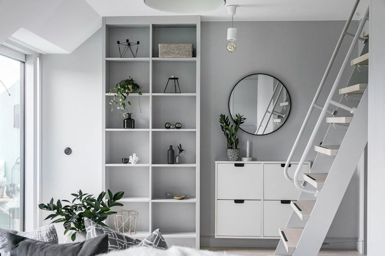 Biblioteca gris y mueble flotante blanco complementan la decoración del living