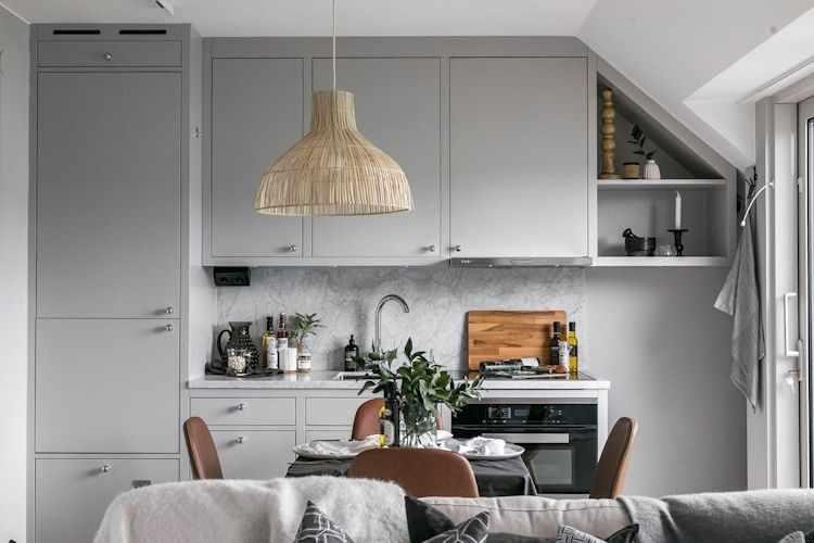 Cocina con muebles y alacenas pintados de gris y mesada con alzada de mármol de carrara