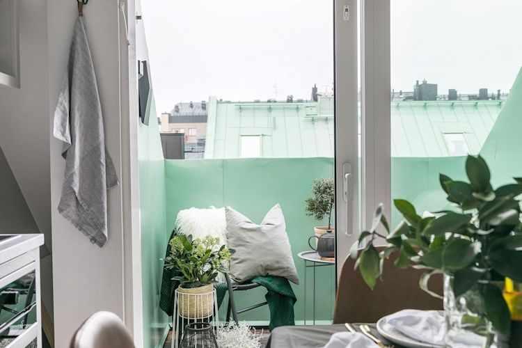 Balcón con paredes en verde claro incorporan color al interior desde afuera