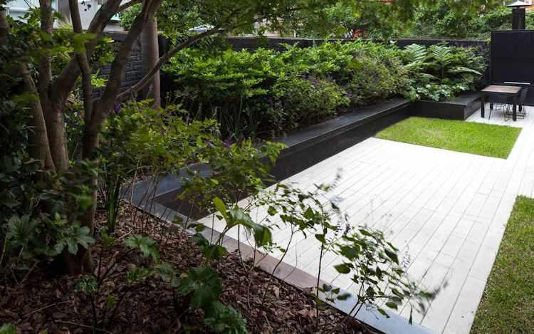 El muro y borde del cantero en gris oscuro contrasta con el verde de las plantas y hace que resalten más.