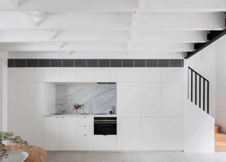 Cocina pequeña con armarios que esconden el lavarropas y la TV, creando un diseño de estilo minimalista