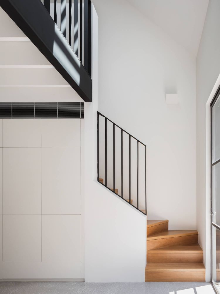 Escalera hacia la planta alta en el entrepiso con diseño minimalista y escalones de madera para sumar color