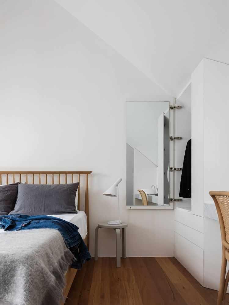 Un cálido dormitorio con pisos de madera y cama haciendo juego