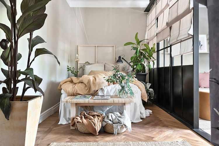 Dormitorio separado del ambiente principal mediante división fija de madera y vidrio repartido