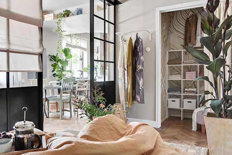 Espacio para el dormitorio del monoambiente con decoración que incluye plantas, alfombras y elementos coloridos