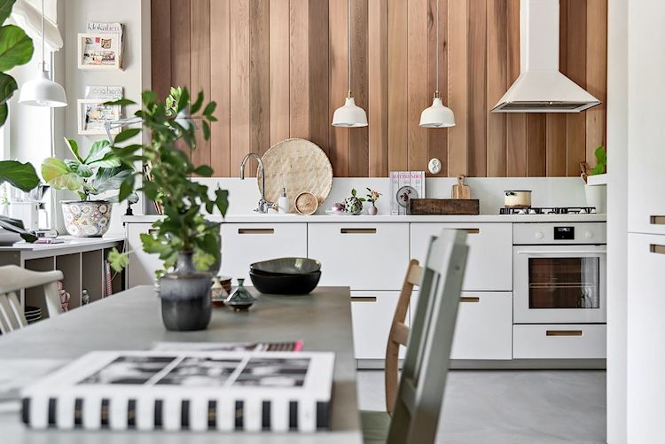 Cocina del monoambiente con pared revestida con listones de madera en lugar de azulejos