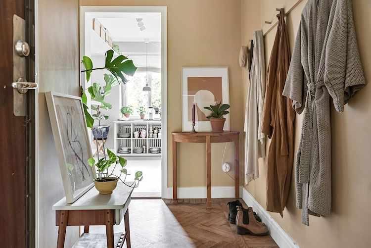 Pasillo de entrada con decoración cálida y muebles vintage